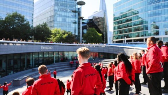 Volunteer mentors in red jackets on the steps of London's City Hall
