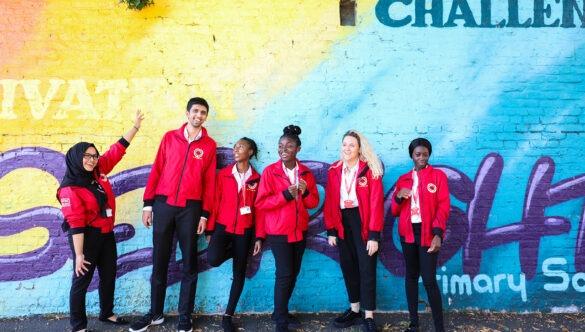 Volunteer mentors against a graffiti wall