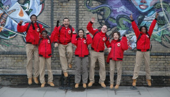 Group of volunteer mentors in red jackets standing against a graffiti wall and cheering