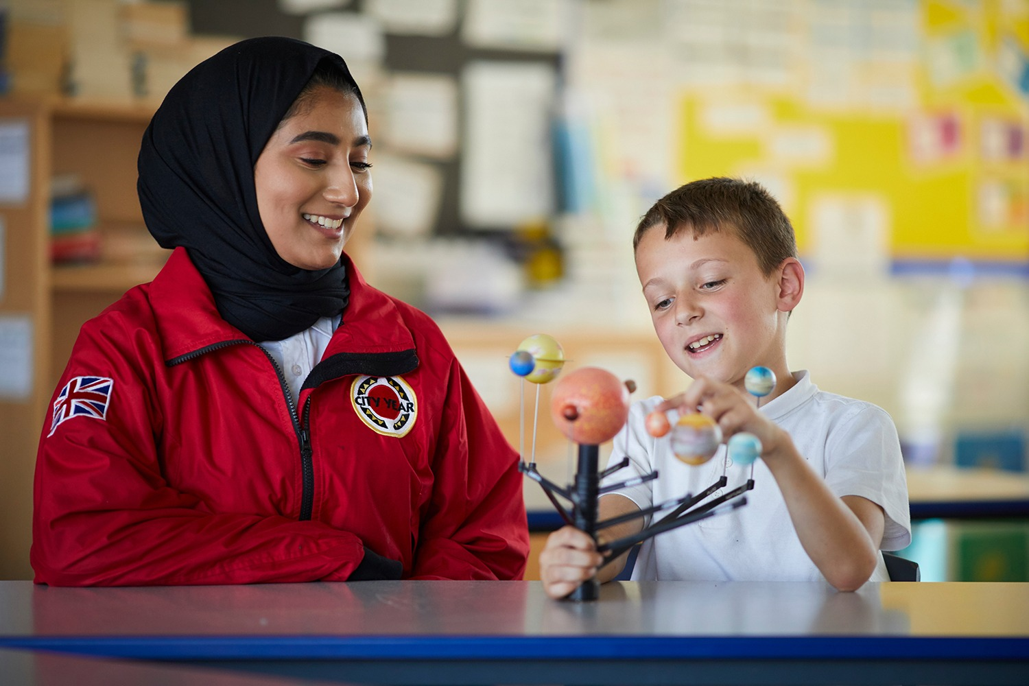 Female volunteer mentor in a hijab working with a pupil on a science project