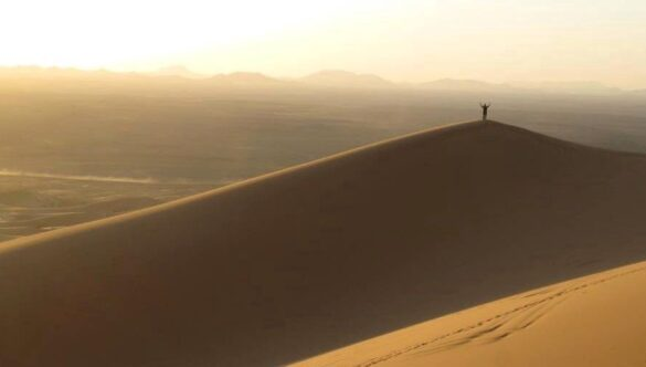 Person on top of sand dune
