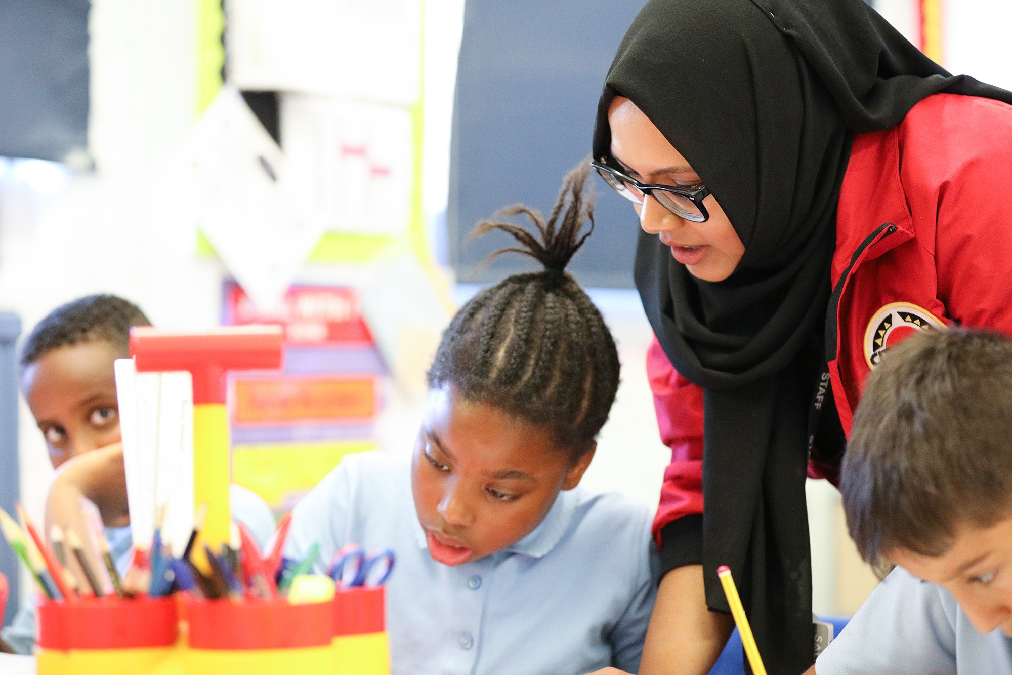 Female volunteer mentor with a hijab leaning over a pupil