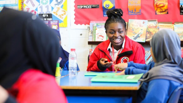 Volunteer mentor in classroom with a pupil