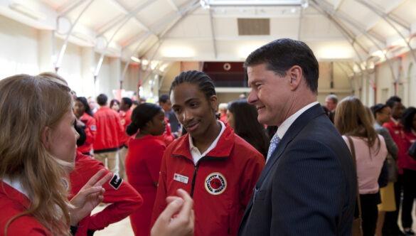 Two volunteer mentors in conversation with Steve Holliday