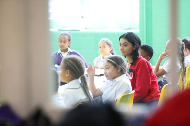 Through the door of a classroom, with a volunteer mentor seated at a table with pupils