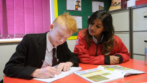 Volunteer mentor working with a pupil with a book open in front of them