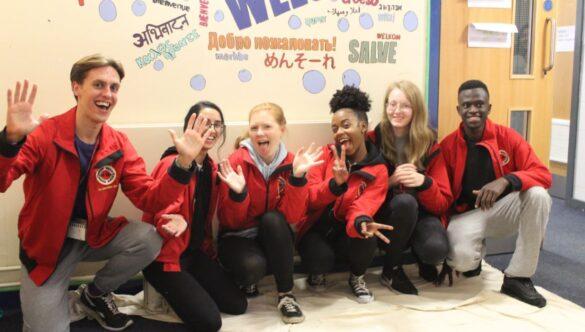 Group of volunteer mentors smiling on the floor of a school