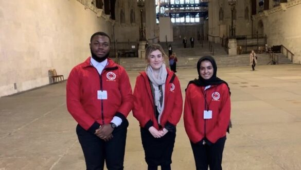 Three volunteer mentors standing outside of Parliament