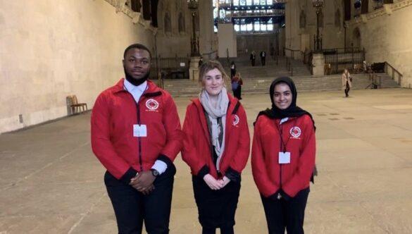 Three volunteer mentors standing outside of Parliament